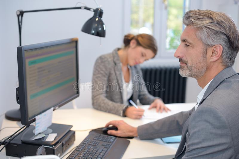 Mature businessman working on computer in office stock photography