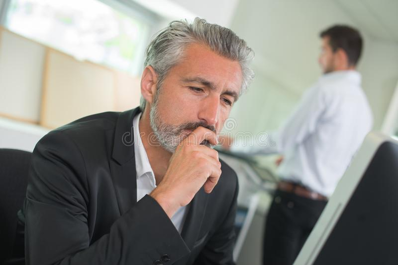 Mature businessman working on computer in office stock image