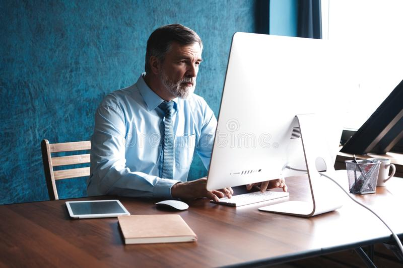 Mature Businessman Working On Computer In Office stock images