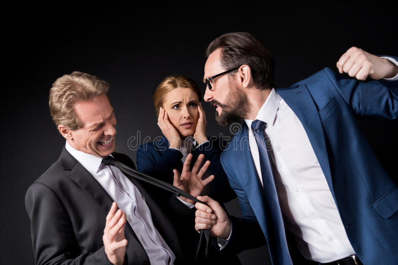 Mature businessmen fighting while scared businesswoman standing behind stock photos