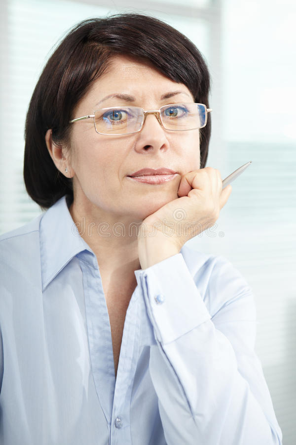 Mature businesswoman. In eyeglasses looking at camera stock photos