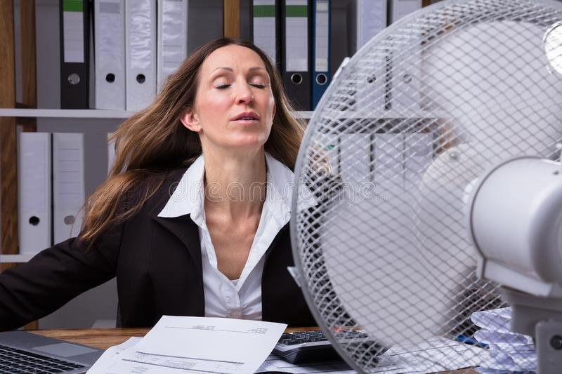 Businesswoman Cooling Herself In Front Of Fan. Mature Businesswoman Cooling Herself In Front Of Fan During Hot Weather stock images