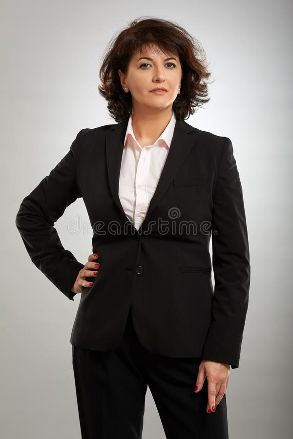 Smiling Businesswoman Leaning Against Whiteboard And