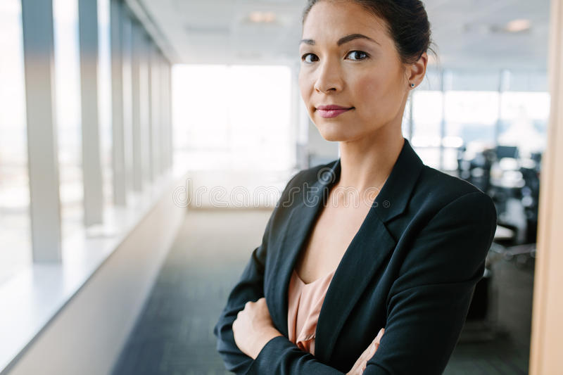 Mature businesswoman in office with her arms crossed stock images