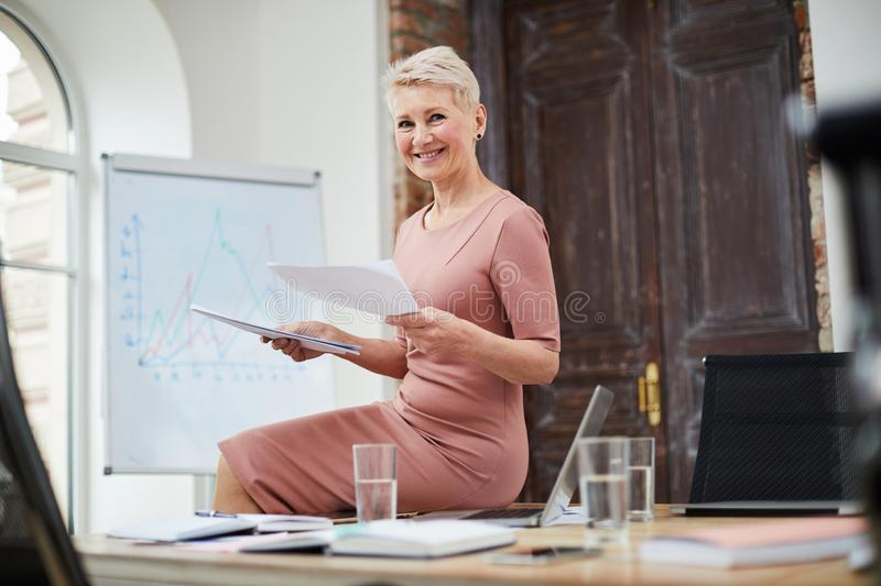 Mature Businesswoman in Office. Portrait of mature businesswoman smiling at camera while sitting on table in office and using digital tablet, copy space stock photo
