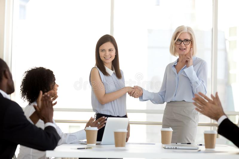 Mature businesswoman shaking hand of employee at company briefing royalty free stock images