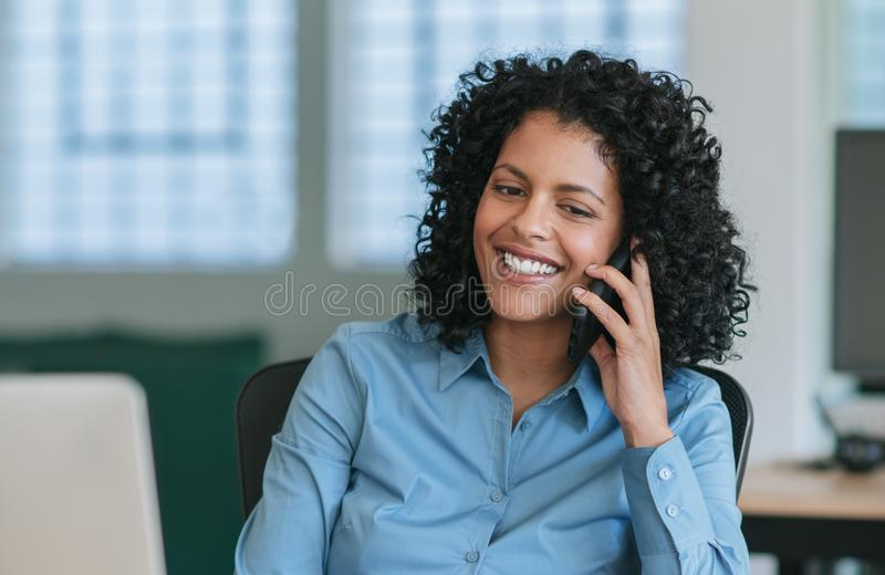 Mature businesswoman sitting at her desk talking on a cellphone stock photos