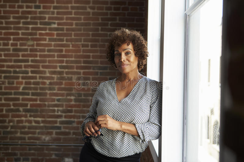 Mature Businesswoman Standing By Office Window royalty free stock image