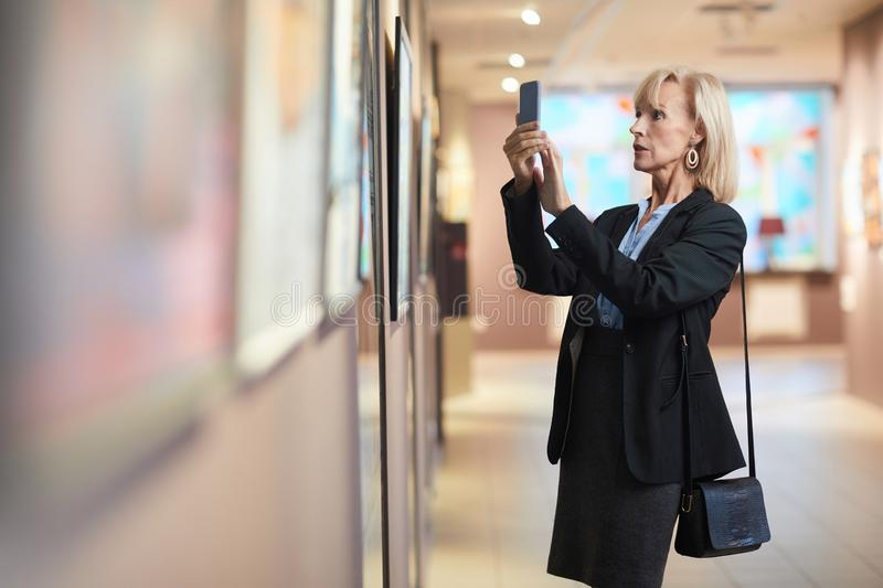 Mature Businesswoman Taking Smartphone Photo of Painting in Gallery stock images