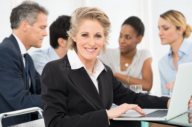 Mature Businesswoman Using Laptop. Portrait Of Smiling Mature Businesswoman Looking At Camera royalty free stock image