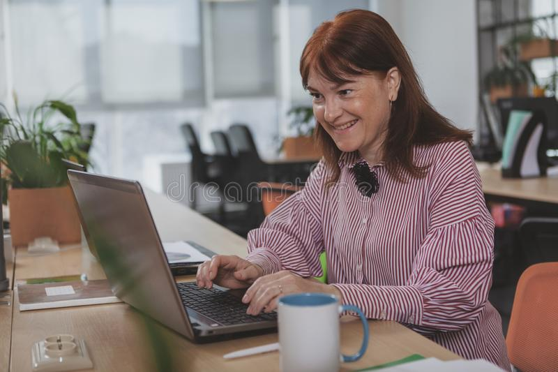 Mature businesswoman working at the office. Cheerful mature businesswoman smiling, working at her office. Lovely female entrepreneur typing on her laptop, copy stock photography