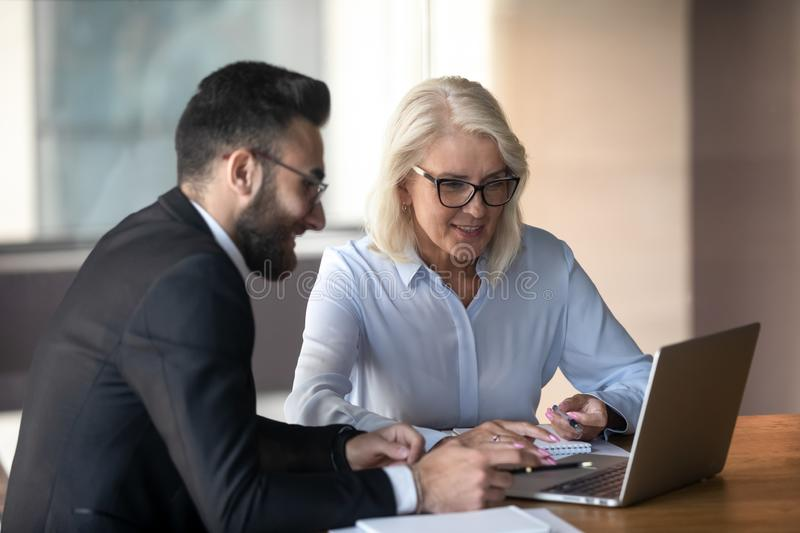 Mature businesswoman and young colleague working on project together. Employees using laptop, discussing strategy, planning, senior mentor training teaching stock images