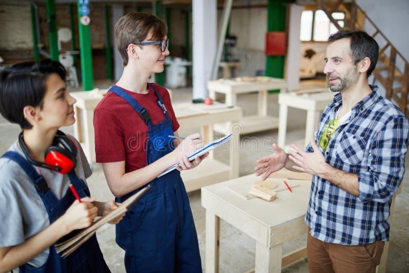 Mature Carpenter Instructing Trainees royalty free stock photos