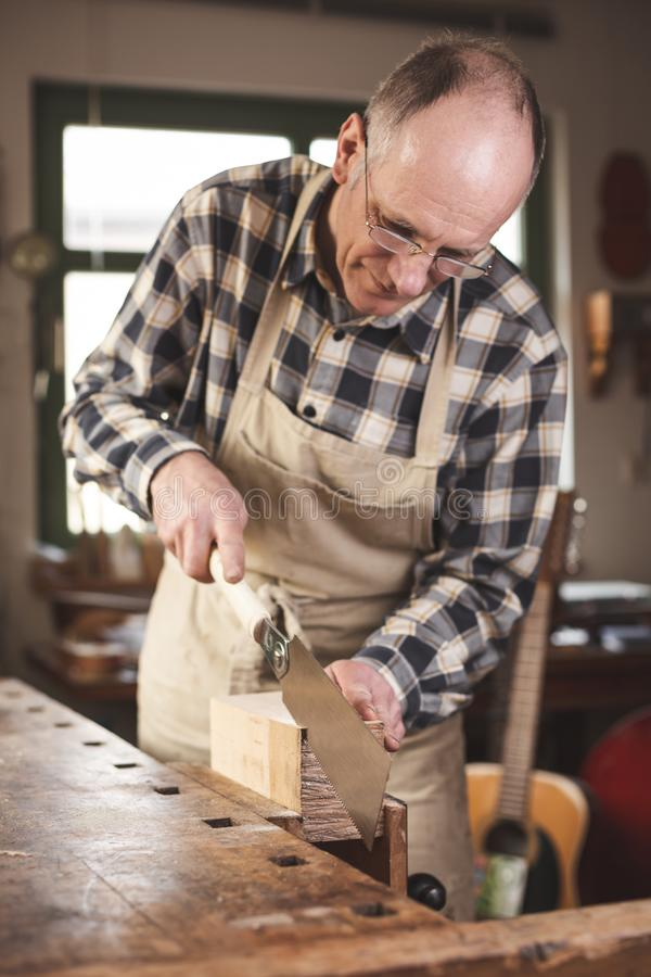 Experienced carpenter sawing with a Japanese hand saw. Mature carpenter using a double edged Japanese pull saw inside his workshop. The craftsman is wearing a stock photo