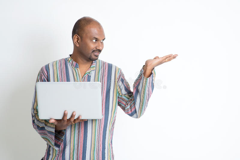 Mature casual Indian man using computer and showing something. Portrait of mature casual business Indian male using laptop computer, hand showing something royalty free stock photography