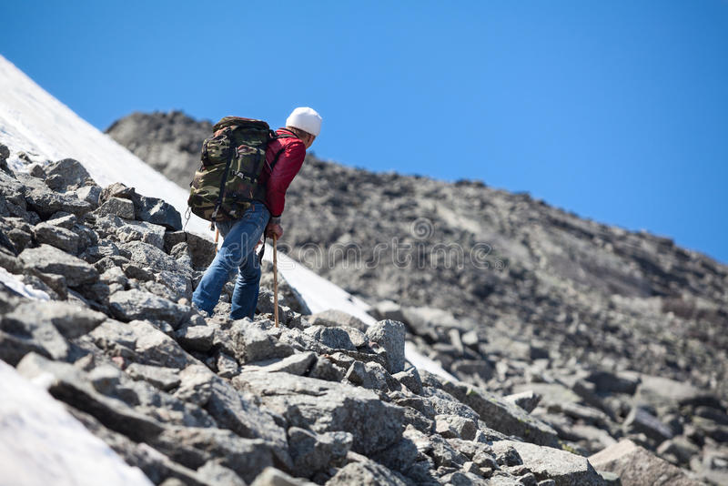 Mature Caucasian hiker looking at the mountains top while resting on the steep slope stock image
