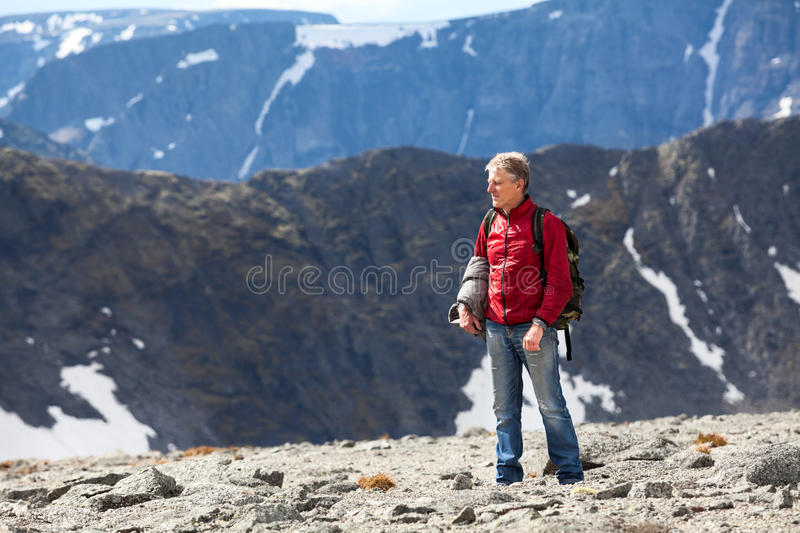 Mature Caucasian man hiking on the mountain plateau along, copy space stock images