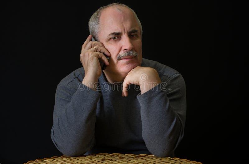 Mature Caucasian man listening cellular phone royalty free stock photos