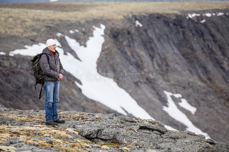 Mature Caucasian man mountain tourist standing on cliff and looking on stone valley, copy space royalty free stock photo