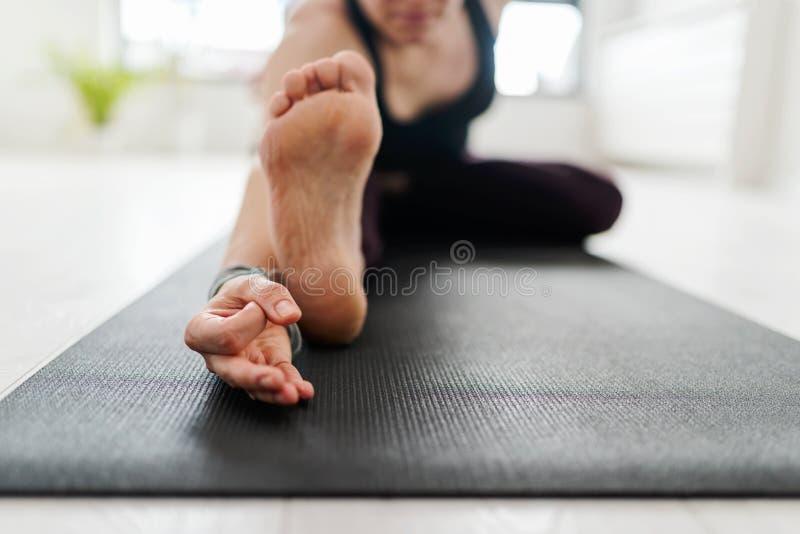 Mature Caucasian woman practicing yoga on livingroom floor stock images