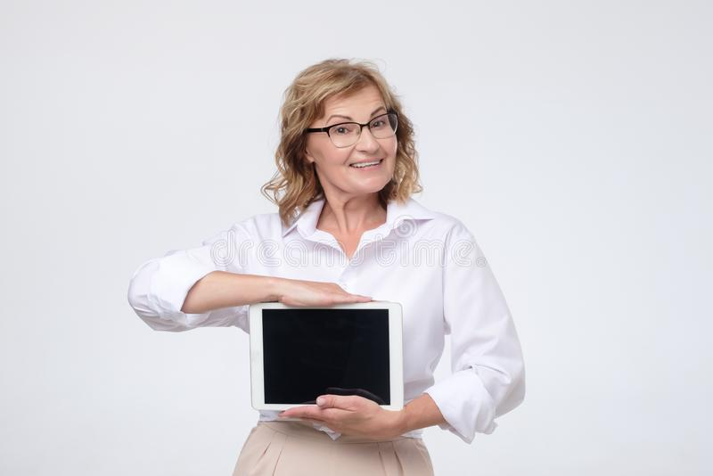 Mature caucasian woman shows a screen digital tablet royalty free stock image