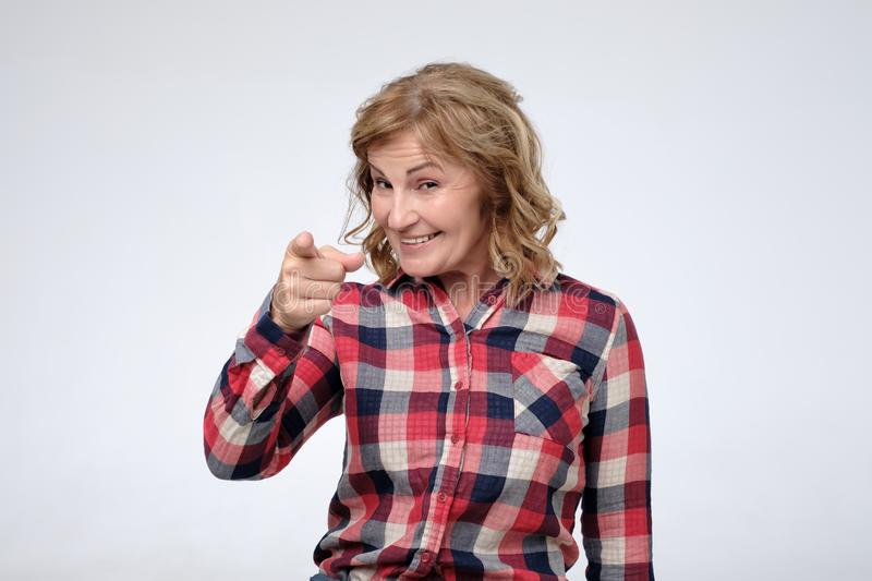 Mature caucasian woman wearing casual shirt smiling pointing at camera with index fingers. stock image