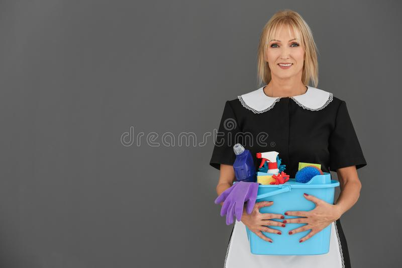 Mature charwoman with cleaning supplies. On grey background royalty free stock image