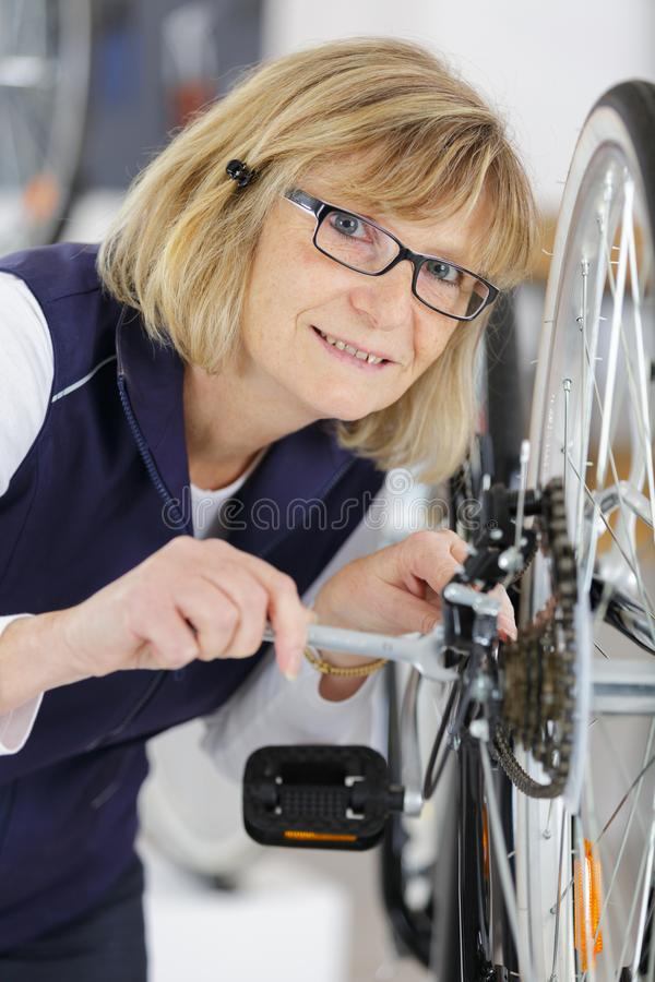 Mature cheerful woman tightening bicycle wheel screws in garage stock photography