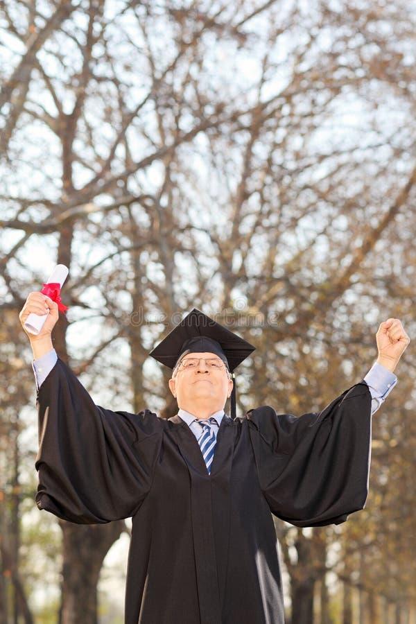 Mature College Graduate Gesturing Success In Park Stock Photo