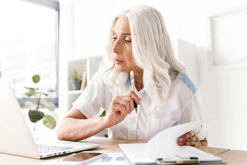 Mature concentrated woman writing notes. stock images