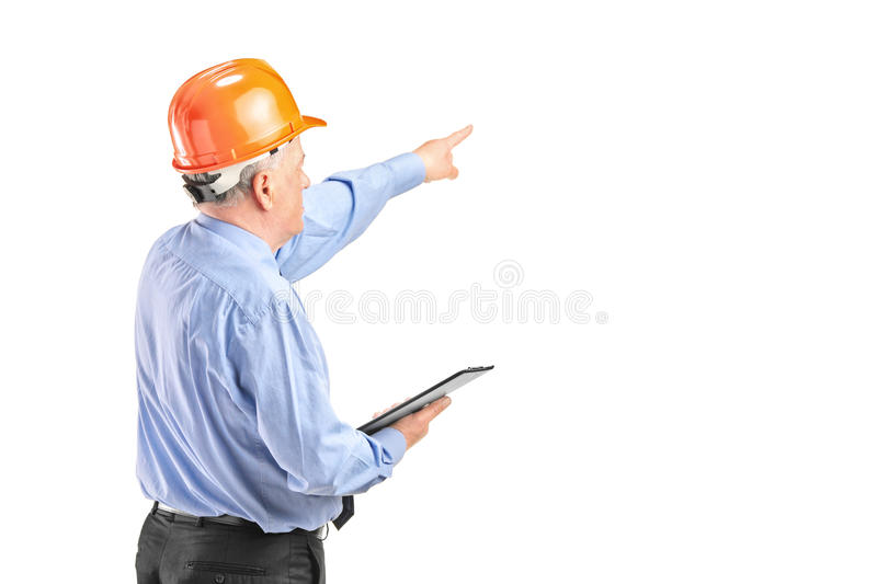 Mature construction worker holding a clipboard stock image