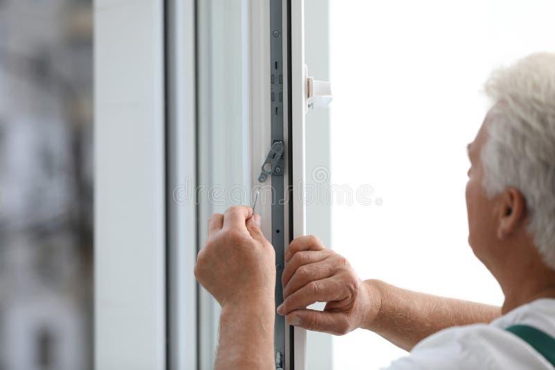 Mature construction worker repairing plastic window, closeup stock images