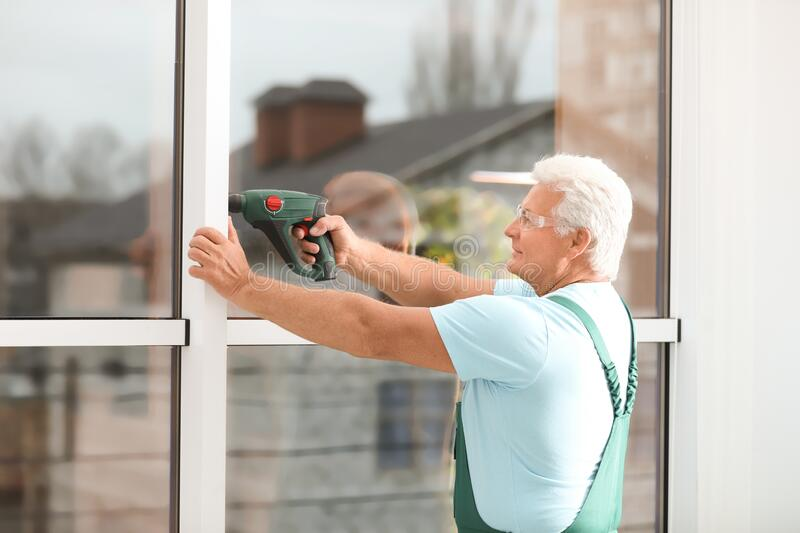 Mature construction worker repairing plastic window with electric screwdriver stock photography