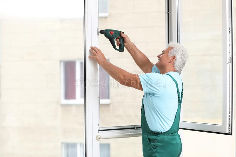 Mature construction worker repairing plastic window with electric screwdriver stock images