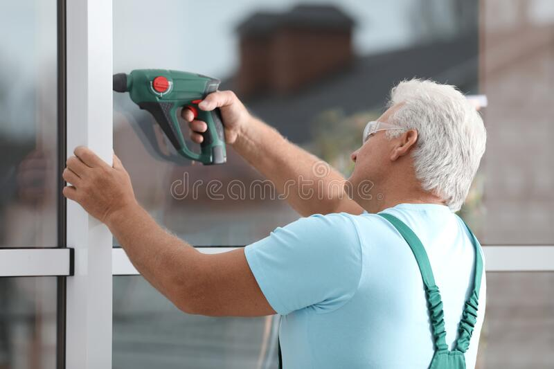 Mature construction worker repairing plastic window with electric screwdriver royalty free stock images