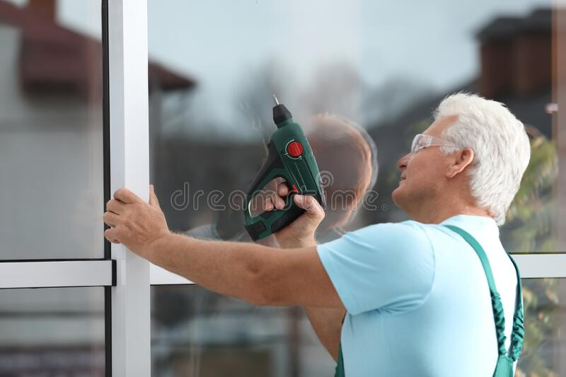 Mature construction worker repairing plastic window with electric screwdriver royalty free stock photos