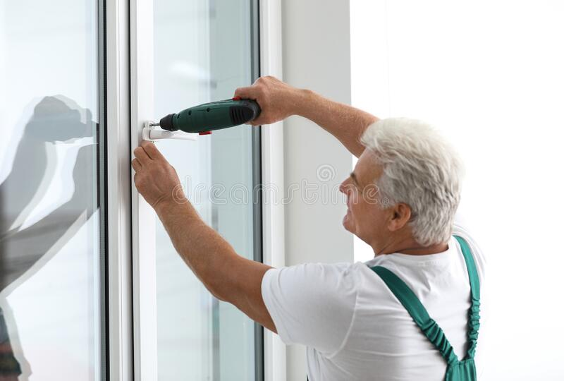 Mature construction worker repairing plastic window with electric screwdriver royalty free stock photo