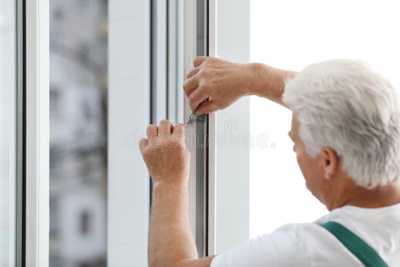 Mature construction worker repairing plastic window stock photo