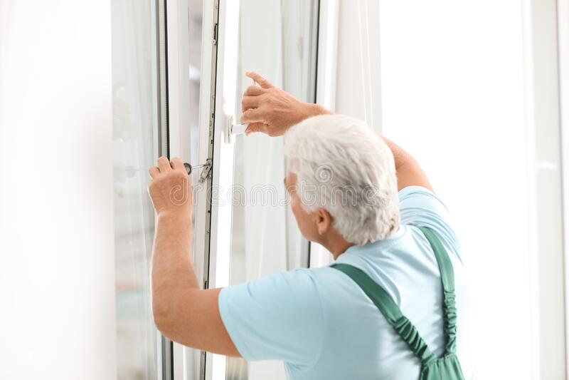 Mature construction worker repairing plastic window with screwdriver indoors stock image
