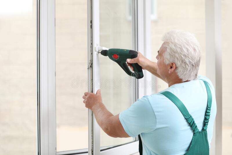 Mature construction worker repairing plastic window with screwdriver indoors royalty free stock photography