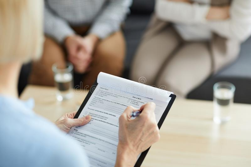 Putting ticks in document. Mature counselor with pen putting ticks in document while filling it in during family consultation stock photos