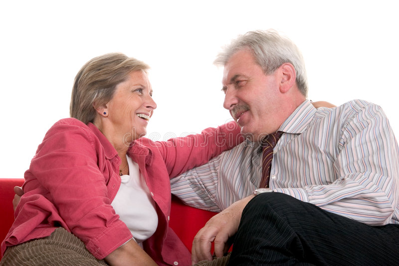 Mature couple. An adult couple sits on the couch and smiles to each other royalty free stock photo
