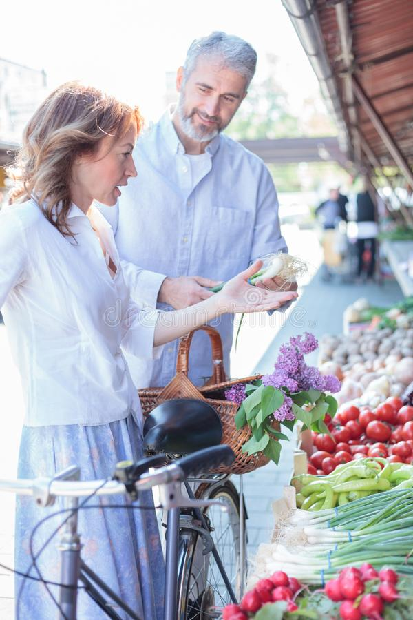 Mature couple buying fresh organic vegetables in an open air marketplace royalty free stock image