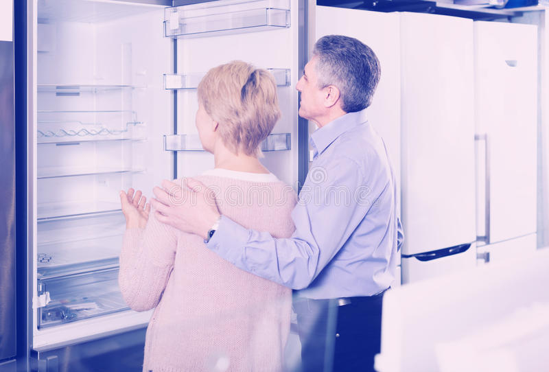 Mature couple chooses refrigerator in store stock image