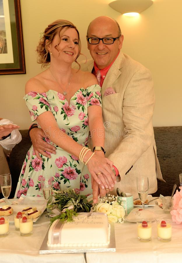 Mature couple cutting wedding cake. Together at reception royalty free stock images