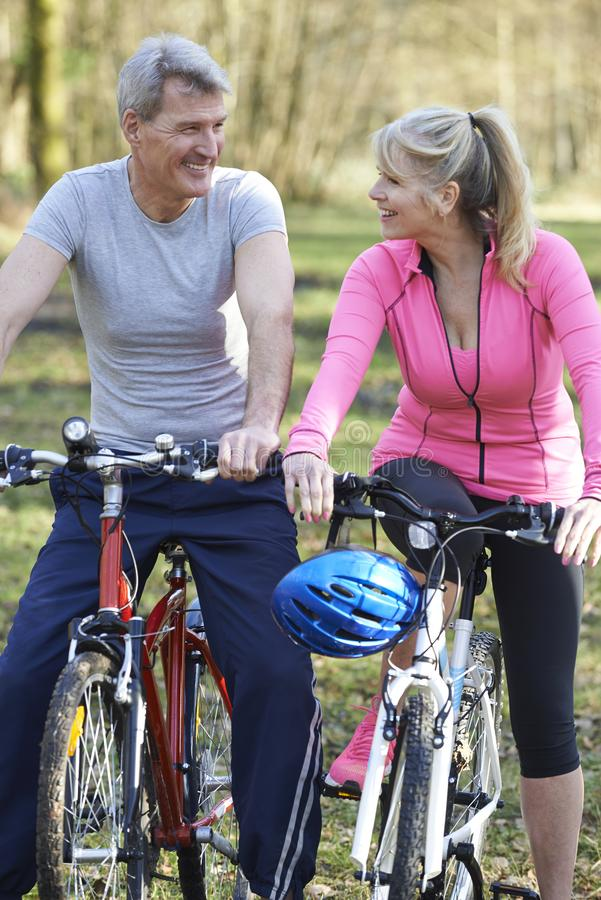 Mature Couple On Cycle Ride In Countryside Together stock images