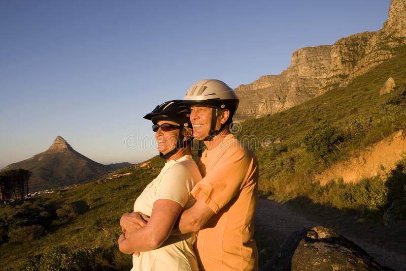 Mature couple, in cycling helmets, standing on mountain trail, looking at scenery, man embracing woman, side view. Mature couple, in cycling helmets, standing on stock photography