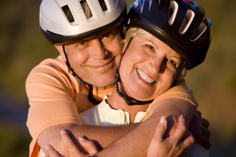 Mature couple, in cycling helmets, standing on mountain trail, man embracing woman, smiling, close-up, portrait. Mature couple, in cycling helmets, standing on stock photos