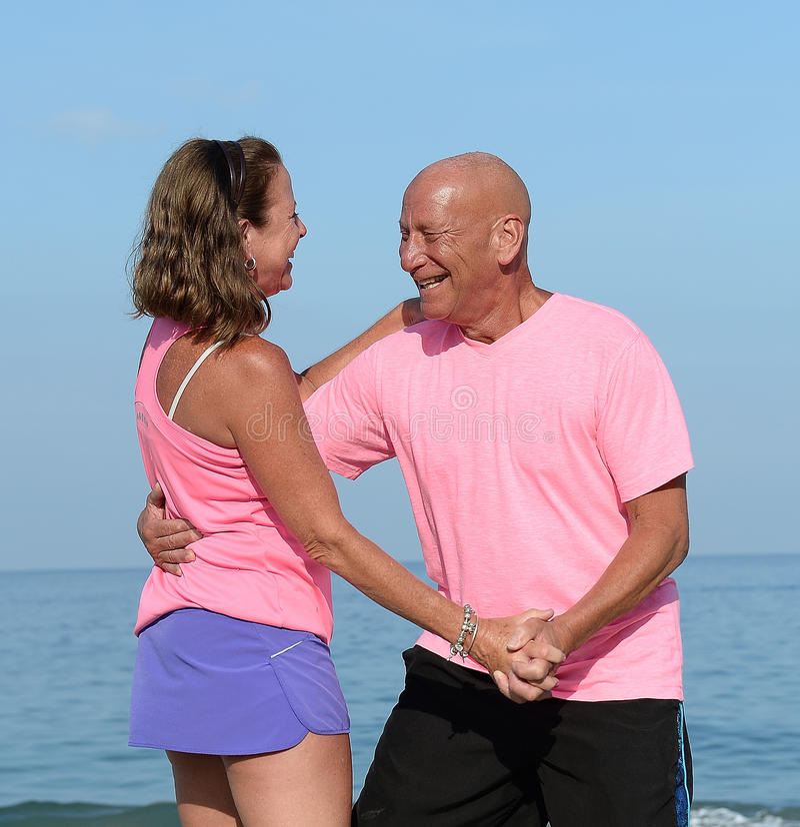 Mature couple dancing at seashore royalty free stock photo