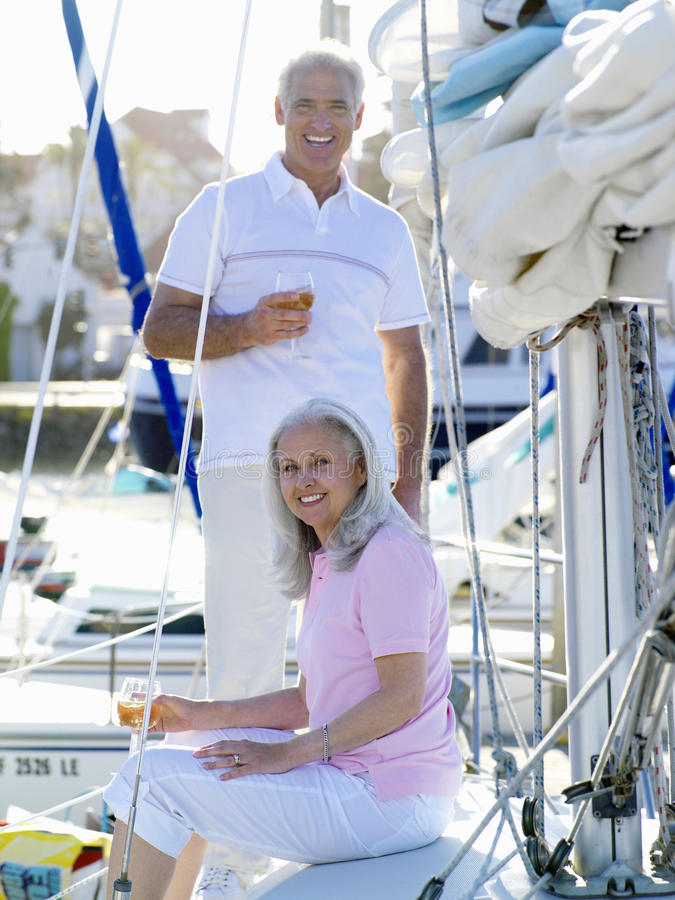 Mature couple on deck of boat with drinks, smiling, portrait stock images